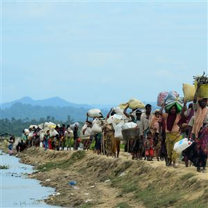 In this October 19, 2017, file photo, Rohingya refugees who were stranded walk near the no man's land area between Bangladesh and Myanmar in the Palongkhali area next to Ukhia.