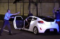Puerto Rico Police Officer Heriberto Soto  shouts commands to the passengers and driver after a late-night high speed chase through San Juan on Oct. 18, 2017.
