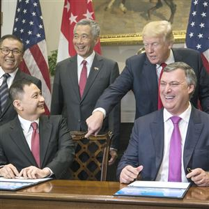 Boeing executive vice president Kevin McAllister (R) and Singapore Airlines CEO Goh Choon Phong (C-L) along with President Donald Trump (C-R) and Singapore's Prime Minister Lee Hsien Loong (C) attend a signing ceremony for airplane sales in the Roosevelt Room at the White House on October 23, 2017 in Washington.