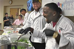 The Steelers'  B.J. Finney laughs as Arthur Moats places shocked broccoli in the food processor as they make a pesto  during the Healthy Cooking Demonstration at Magee-Womens Hospital of UPMC in Oakland on Tuesday. They were preparing Greek chicken with tomatoes, peppers, olives and feta and orecchiette with broccoli rabe pesto for the crowd.