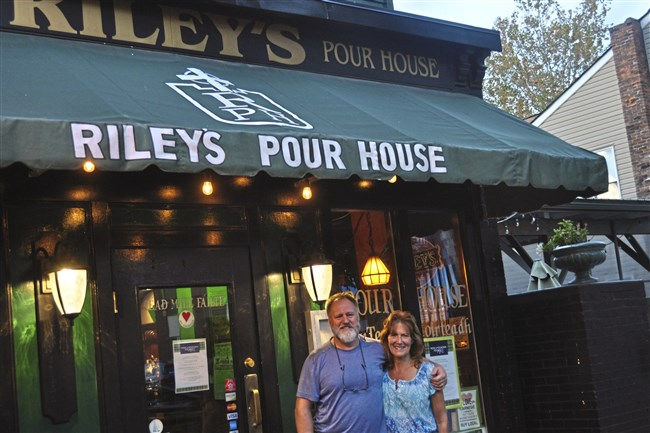 Owners Jim and Cheryl Riley in front of Riley's Pour House on East Main Street in Carnegie.