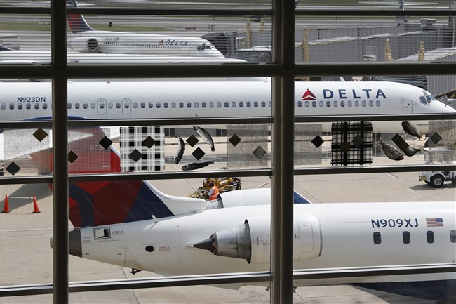 "FILE - In this Monday, Aug. 8, 2016, file photo, Delta Air Lines planes are parked at Ronald Reagan Washington National Airport, in Washington.  A bogus pet-shipping website that tricks people into thinking they're dealing with Delta Air Lines is also linked to a scam that preys on people hoping to buy dogs such as Chihuahuas, poodles and corgis, the airline says in a court filing. Delta, one of the world's largest airlines says its wide-ranging investigation into the pet shipping website uncovered a ""larger criminal scheme."" Delta filed a federal lawsuit last month over a website that it says tricks people into thinking they're dealing with the airline when arranging for their pets to fly on jets. The airline says the site — DeltaPetTransit.com — is designed to look like a Delta site and uses the airline's logos and pictures of its planes. (AP Photo/Carolyn Kaster, File)"