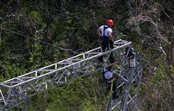 In this Oct. 15, 2017, file photo, Whitefish Energy Holdings workers restore power lines damaged by Hurricane Maria in Barceloneta, Puerto Rico.