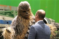 Britain's Prince William, talks with the Star Wars character Chewbacca during a tour of the Star Wars sets at Pinewood studios in Iver Heath, west of London on Tuesday April 19, 2016. Prince William and Prince Harry toured Pinewood to visit the production workshops and meet the creative teams working behind the scenes on the Star Wars films.