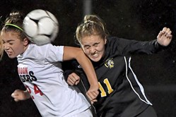 Moon's Delaney Snyder goes for a header against Montour's Samantha White Monday night at West Allegheny High School in the WPIAL girls soccer semifinals.