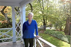 Diane Kamenar leans on the railing of her side porch in Rosslyn Farms. She is a runner-up in the large category of the Great Gardens Contest.