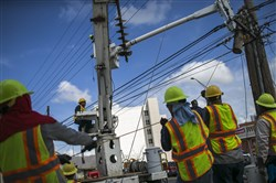 In this file photo, Puerto Rico Electric Power Authority employees work to re-establish power after Hurricane Maria in Caguas, Puerto Rico, on Oct. 7, 2017.