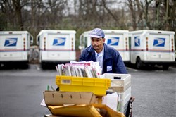 In this Feb. 7, 2013 file photo, a U.S. Postal Service letter carrier gathers mail to load into his truck before making his delivery run in the East Atlanta neighborhood in Atlanta.