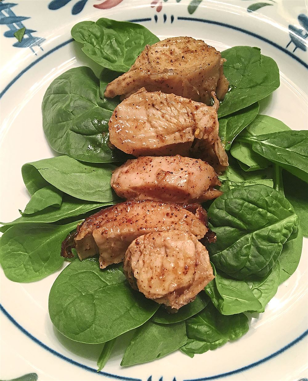 Turkey with a rum glaze on a bed of leaf spinach.