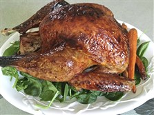 Glistening with plum glaze, turkey is plated with roasted carrots and spinach.