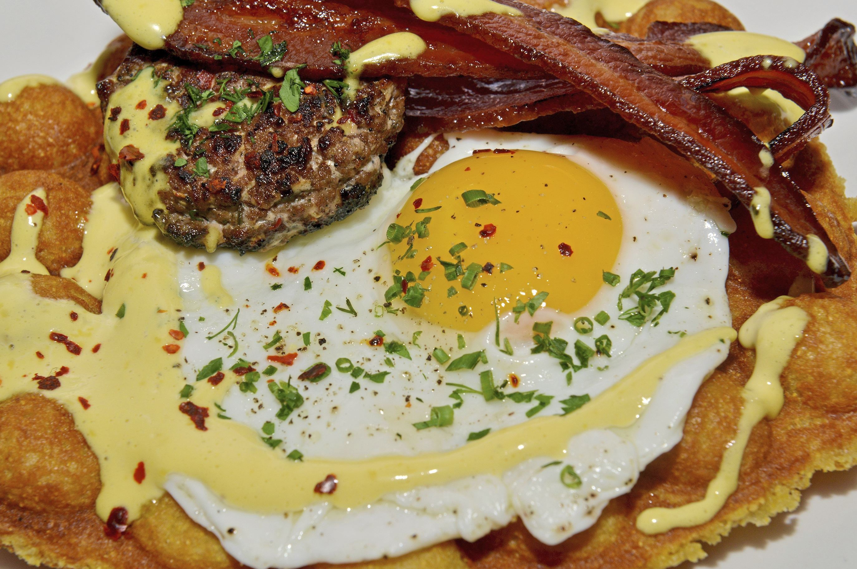 20171101ppTheWhale7MAG-10 Savory bubble waffles with bacon, fried egg, sausage, potatoes and Hollandaise prepared by Dennis Marron at or, The Whale in the Distrikt Hotel, Downtown.