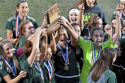 Penn-Trafford players raise the WPIAL trophy after their dramatic win against Norwin Saturday at Highmark Stadium.