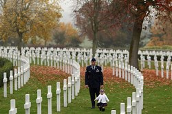 Joshua Donahue walks with his daughter Addelyne through the Cambridge American Cemetery in Madingley, England.