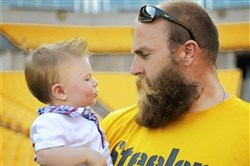 Former Steelers defensive end Brett Keisel sizes up Sam Bell during a 2013 event for veterans at Heinz Field. Sam's father, Jason Bell, 29, served with the Army in Iraq and Afghanistan.
