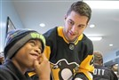 Pittsburgh Penguins player Conor Sheary serves a plate of food to James Jones, 9, of Homestead on Nov. 13 at the Rainbow Kitchen in Homestead.