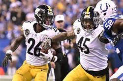 Le'Veon Bell gets a block from Roosevelt Nix on Sunday.