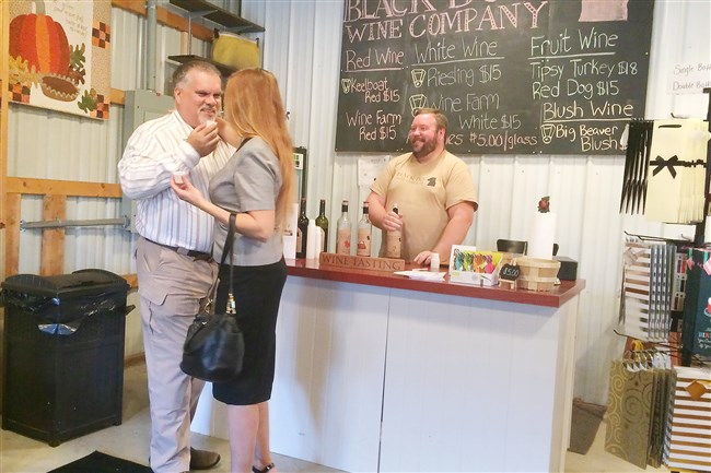 Jim and Irene Rozum of Imperial enjoy a moment, and tastes of his nephew Mark Rozum's wines at Mark Rozum's new tasting room in North Fayette for his Black Dog Wine Co.