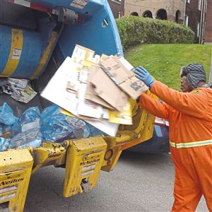 Donald King, of Sheridan, throws cardboard into the back of a garbage truck as items are collected November 14, 2017 in Squirrel Hill.