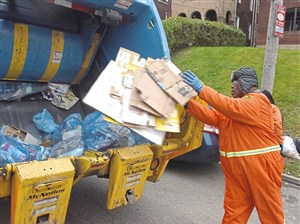 Donald King of Sheridan puts recyclables in the back of a garbage truck.