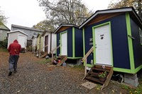 In this photo taken Nov. 9, 2017, a resident walks past a row of tiny houses at a homeless encampment in Seattle where full-size homes stand behind.