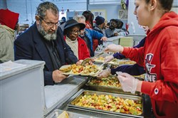Abbas Elfatlawi, left, and Jean McHenry are served meals at the Jubilee Soup Kitchen. The Uptown center serves about 100 meals a day to the needy.