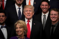 President Donald Trump and Education Secretary Betsy Devos pose for photographs with members of the National Collegiate Athletic Association's champion University of Florida baseball team in the East Room of the White House on November 17, 2017, in Washington.