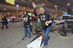 Bryan Morgan of Chippewa and Craig Jeffers of Beaver play cornhole before the Steelers game on Thursday outside of Heinz Field in the North Shore.