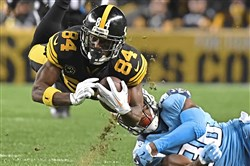 The Steelers' Antonio Brown makes a diving catch against the Titans, one of 10 on the night. The greatest receiver in Steelers history also scored three touchdowns in the 40-17 win.