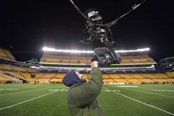 NBC engineer Jake McGrath cleans the lens of one of the two SkyCams used for tonights  Steelers vs. Tennessee Titans game Thursday, November 16, 2017, at Heinz Field.