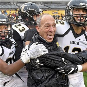 Quaker Valley's Demetrios Perez and Michael Aspiotes hug head coach Jerry Veshio after defeating Aliquippa in the WPIAL 3A championship at Heinz Field Saturday, November 18, 2017 in Pittsburgh.