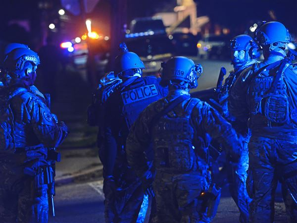 SWAT members prepare to search the neighborhood where at least one police officer was shot Friday, November 17, 2017, in New Kensington.