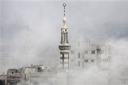 Smoke covers buildings following an airstrike Saturday on the rebel-held town of Arbin in the Eastern Ghouta region on the outskirts of Damascus, Syria.
