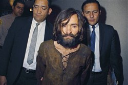 FILE - In this 1969 file photo, Charles Manson is escorted to his arraignment on conspiracy-murder charges in connection with the Sharon Tate murder case. Authorities say Manson, cult leader and mastermind behind 1969 deaths of actress Sharon Tate and several others, died on Sunday, Nov. 19, 2017. He was 83.