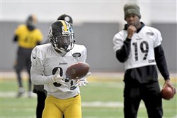 Steelers Antonio Brown pulls in a pass in front of JuJu Smith-Schuster during practice Monday at UPMC Rooney Sports Complex.