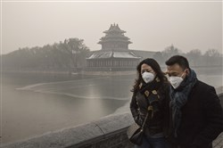 A couple wear protective masks as they walk outside the Forbidden City in heavily polluted Beijing, China.