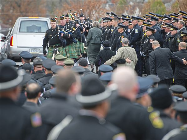 The hearse and mourners arrive for the funeral service for slain New Kensington Officer Brian Shaw Wednesday at Mount Saint Peter Church in New Kensington.