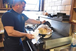 Lt. Damian Szuch, of the City of Pittsburgh Bureau of Fire's  Engine 17 in Homewood  takes his 30 lb. turkey out of the oven to check it for the Thanksgiving feast on Thursday.