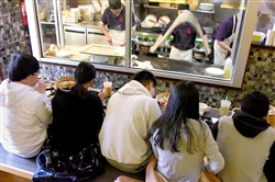 People sit at the counter while Jung Liu throws and stretches a long strand of dough to make noodles at  Everyday Noodles in Squirrel Hill.