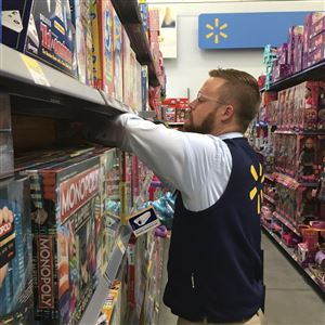 In this Wednesday, Nov. 23, 2016, file photo, Denver Walmart Supercenter employee Aaron Sanford stocks toys on shelves in preparation for a Thanksgiving night rush that kicks off Black Friday weekend.