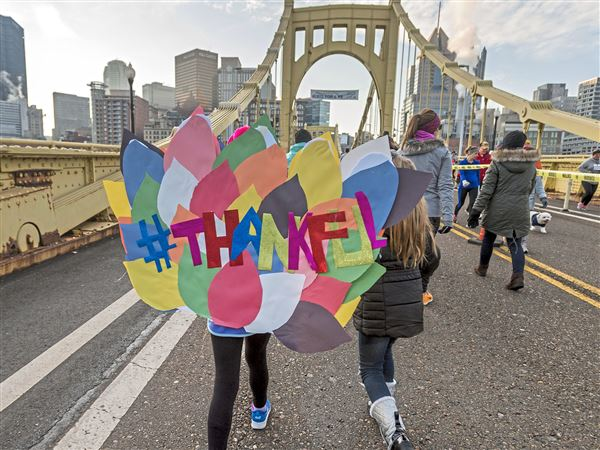 Competitors cross the Roberto Clemente Bridge during the PNC YMCA Turkey Trot on Thanksgiving morning.