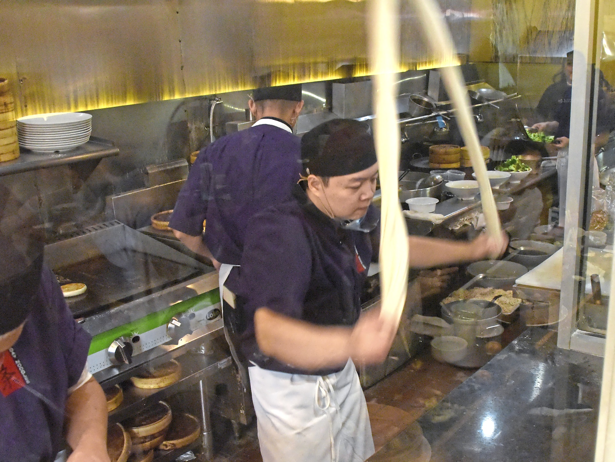 20171123dsEverydayDoodlesFood01 Jung Liu stretches and slams a long strand of dough to make noodles at Everyday Noodles in Squirrel Hill.