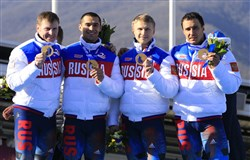 This file photo taken on February 23, 2014 shows, left to right, gold medallists, Russia-1 four-man bobsleigh, pilot Alexander Zubkov, pushman Aleksei Negodaylo, pushman Dmitry Trunenkov and brakeman Alexey Voevoda celebrating at the Bobsleigh Four-man Medal Ceremony at the Sanki Sliding Center during the Sochi Winter Olympics.
