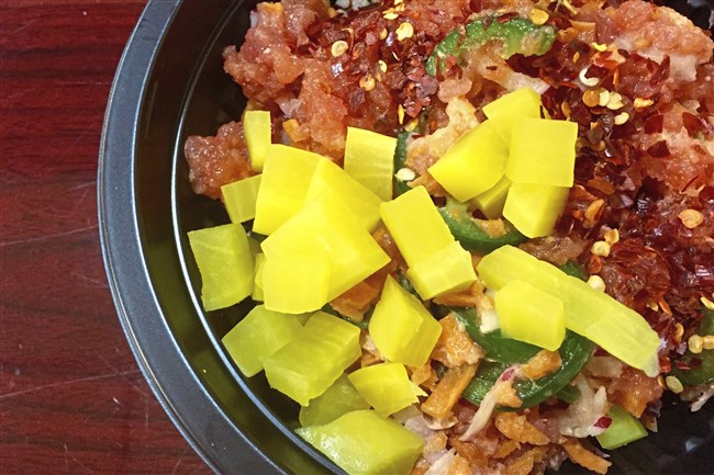 A colorful poke bowl from Pittsburgh Poke, includes spicy tuna, carrot, jalapeno, chili flakes and bright yellow oshinko, a pickled Japanese radish.