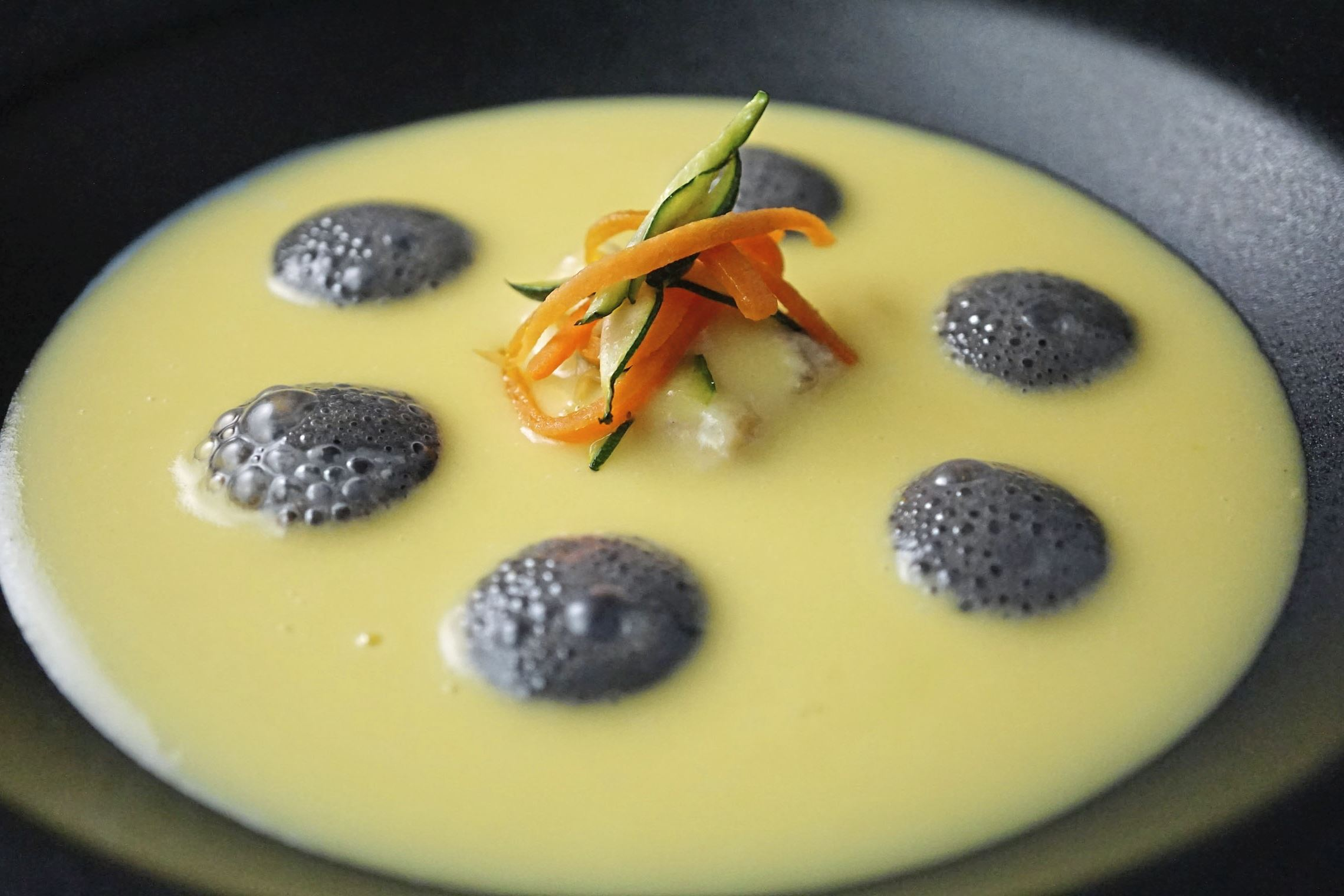 """Saffron Potato Soup with Baccala Vellutata di Patate con Baccala al Nero di Seppia (Creamed Saffron Potato Soup with Baccala and Squid Ink Foam served with Julienne Vegetables), one of the """"seven fishes"""" to be served on Christmas Eve at Senti in Lawrenceville."""