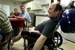 In this August 15, 2006, file photo, Jason Hilton, who has Huntington's disease, sits in on a meeting in Lowell, Mass., of a nonprofit group run by ex-teammates from his high school football team.