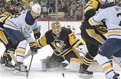 Pittsburgh Penguins Tristan Jarry makes save on the Sabres' Hudson Fasching, Dec. 2, 2017, at PPG Paints Arena. Lately, Jarry has earned his teammates' respect in a big way and has helped the Penguins play more consistent hockey.