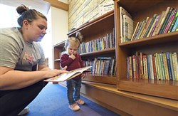 Abigail Keller, 16 months, browses books with her mother, Bridey at the Moulis Children's Library at Children's Hospital of Pittsburgh of UPMC. Bethel Park fourth graders coordinated a book collection for the library.