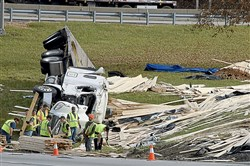 A rig lays on its side after losing a load of lumber on Interstate 376 in Monroeville above Route 22 and between the Pennsylvania Turnpike's toll booths and ramps.