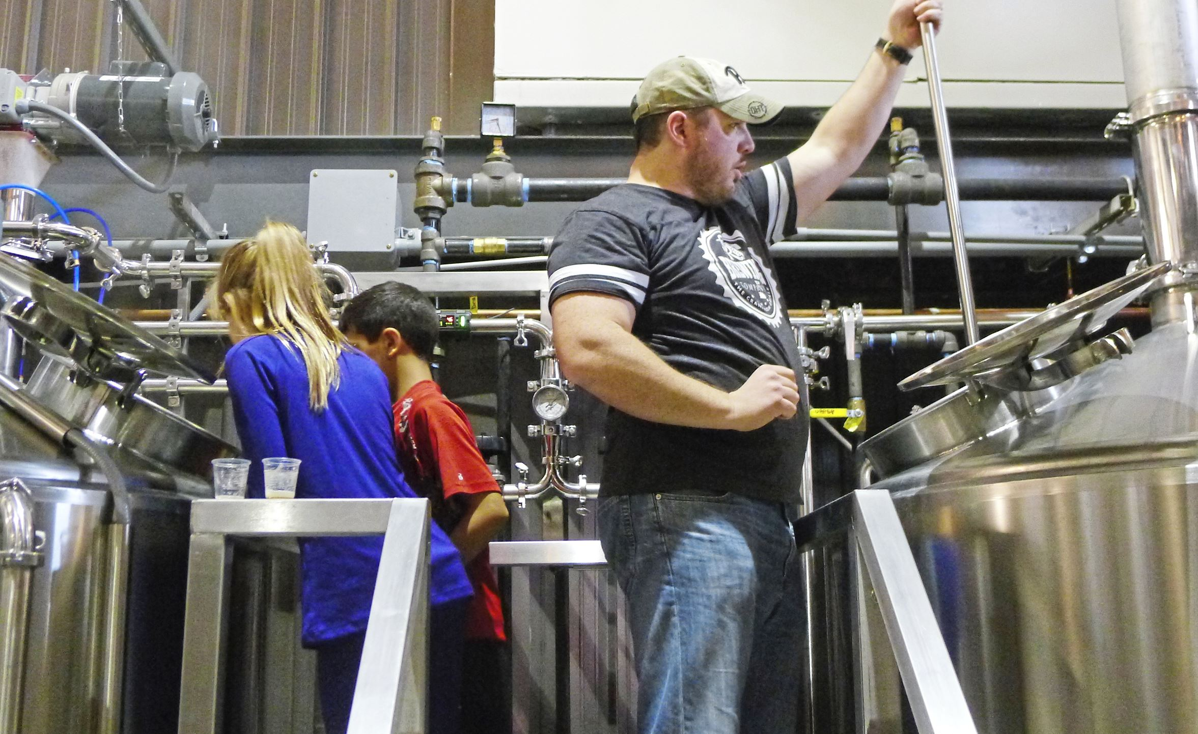 CR BREWING 3-2 With a niece and nephew helping, brewer Bryan McDowell works on one of the first batches of beer in the brewhouse at the new CR Brewing Co. in Neshannock, Pa., near New Castle.