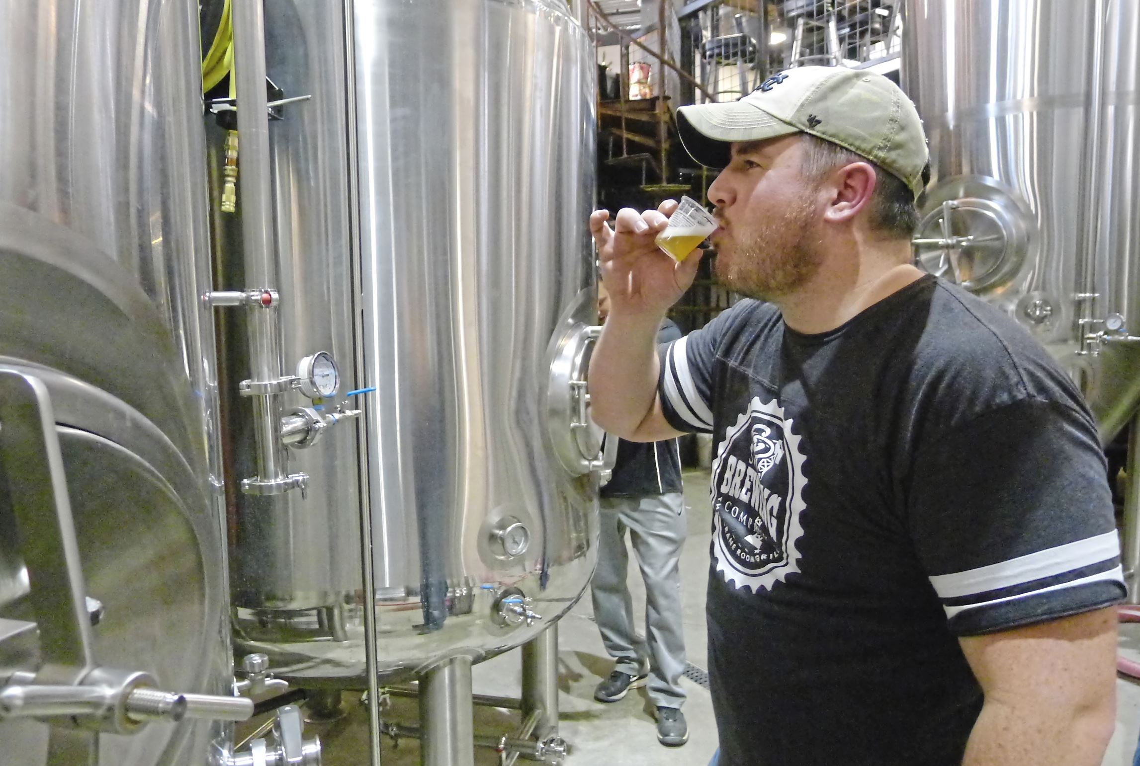 CR BREWING 2-1 Brewer Bryan McDowell takes his first taste of his kolsch after it was carbonated in one of the bright tanks in the brewhouse at the new CR Brewing Co. in Neshannock, Pa..